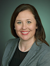 woman wearing grey suit jacket and black top smiling at camera