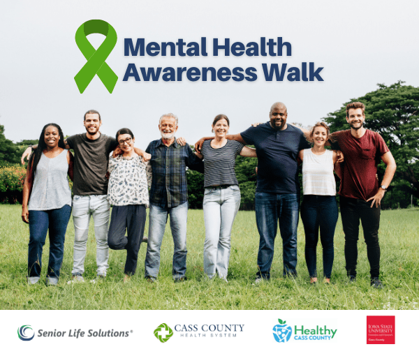 Diverse group standing in grass with arms around each other. text above says Mental Health Awareness walk, and sponsor logos under.